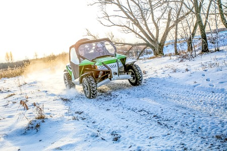 flashy: Omsk, Russia - November 13, 2015: green flashy quad bike on a winter in field off road in sunlight back view