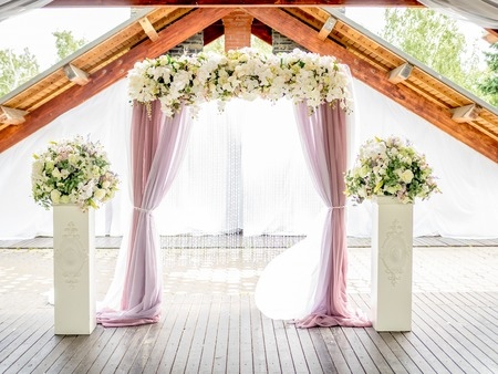 floral wedding arch of white roses and lillies ith purple with curtains Foto de archivo