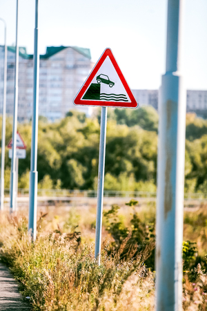 fiscal cliff: road sign of danger falling into the water at sunny day