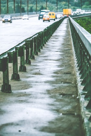 guardrails: wet pedestrian zone on the car bridge at rainy day