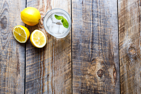 preperation: glass with ice and lemons and mint on wooden table - preperation for lemonade