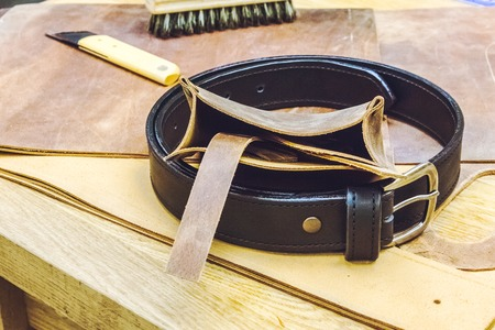 saddler: leather workshop and tools  with black belt on wodden table close up