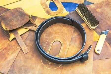saddler: leather workshop and tools  with black belt on wodden table