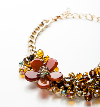gold necklace: necklace made of beads and stones with flower ornament isolated