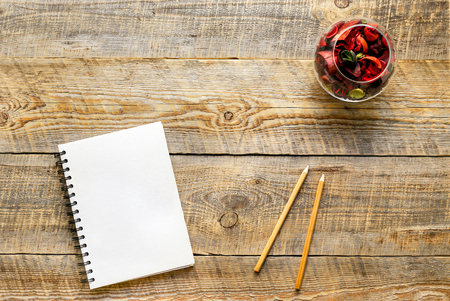 sachets: white notebook with pencil and flower sachets on wooden table