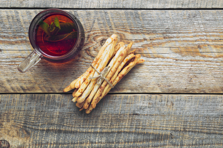 pretzel stick: Heap of cheese bread sticks with cup of tea on wooden table with straw - tasty snack for breakfast in village