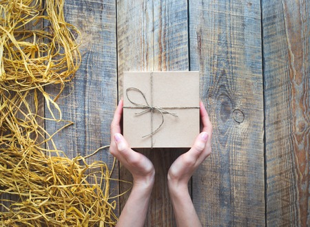 raffia: craft gift box on wooden table with natural raffia or twine with womans hands