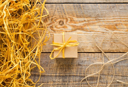 raffia: small raft gift box on wooden table with natural raffia or twine close up