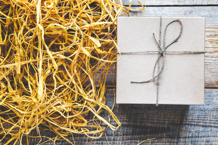 raffia: craft gift box on wooden table with natural raffia or twine close up