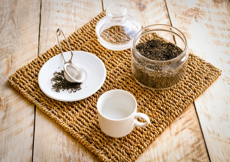 tea strainer: Tea on wicker mat at home wodden table backround with jar and tea strainer Stock Photo