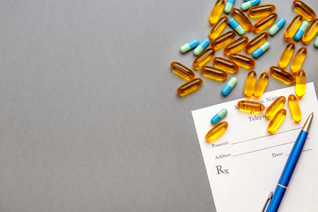 the name of the drug: blank medical prescription and pills on gray background isolated