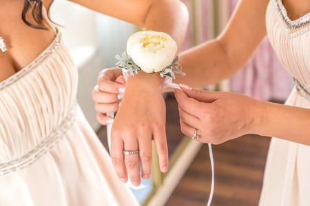 morning routine: morning routine bride putting on the boutonnieres bridesmaids