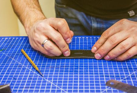 saddler: leather workshop master holds a black belt under table with tools