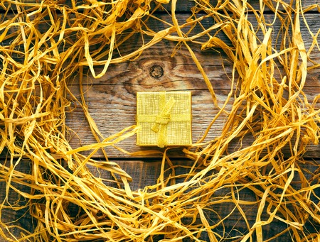 raffia: golden gift box on wooden table with natural raffia or twine
