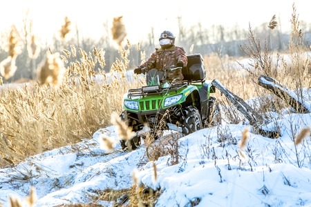flashy: Omsk, Russia - November 13, 2015: green flashy quad bike on a winter in field off road in sunlight Editorial