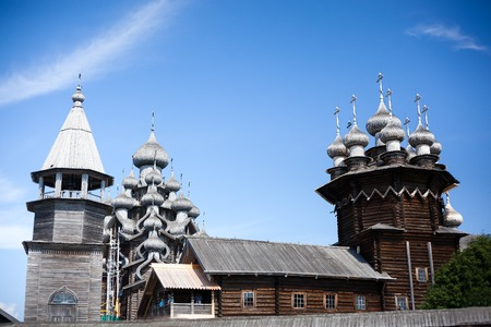 cupolas: beautiful wooden church with cupolas with crosses at summer day under cloudy sky Stock Photo