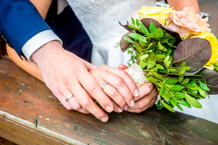 two people with others: The bride and groom hold each others hands with wedding bouquet