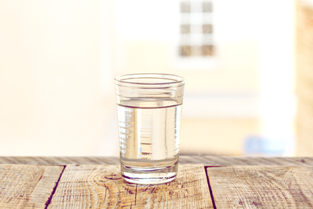 glass cup: glass cup with water on a background of a window
