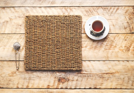 tea strainer: Morning cup of tea on a wooden table on straw napkin with tea strainer - mockup