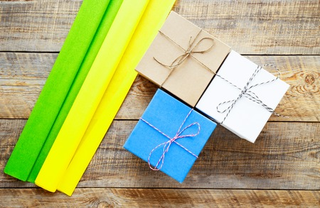 preperation: Colored gift boxes on wooden background with ribbon - preperation Stock Photo