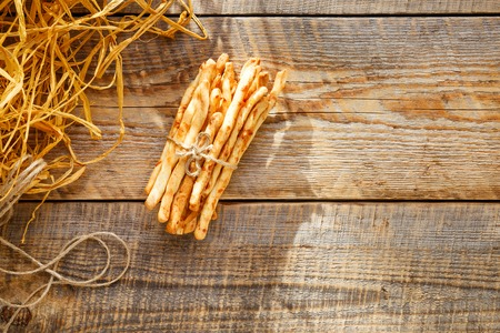 pretzel stick: Heap of cheese bread sticks on wooden table with straw - tasty snack for breakfast in village