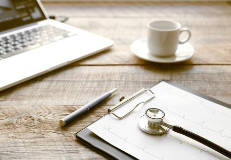 lugar de trabajo médico con un estetoscopio y un ordenador portátil y una taza de café en la mesa de madera