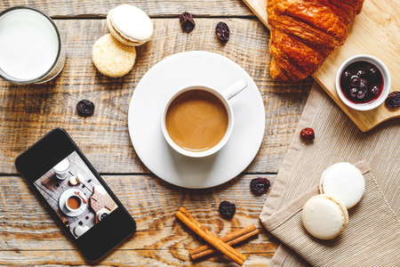mocca: breakfast at home on wooden table with cup of milk coffee, croissants, macaroon and a smartphone Stock Photo