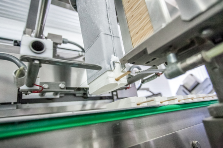 put pressure: Production of white ice-cream - conveyer at factory Stock Photo