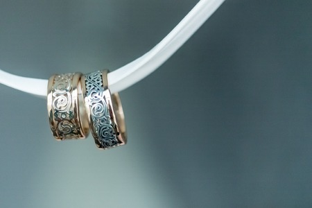 quaint: Two golden quaint wedding rings on white ribbon isolated close up