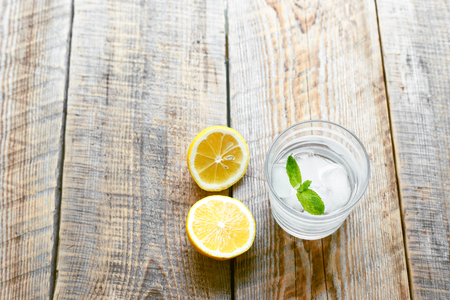 halved  half: glass of lemonade with ice, mint and lemons on wooden table at the morning close up