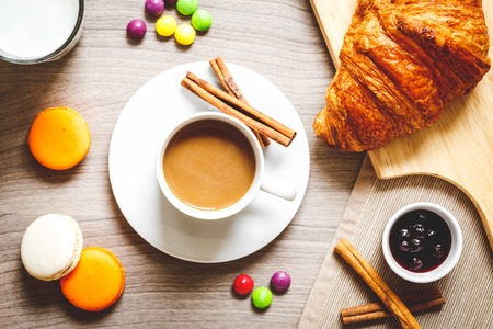 dragee: sweet breakfast with coffee, macaroon, dragee and croissants on wooden table close up
