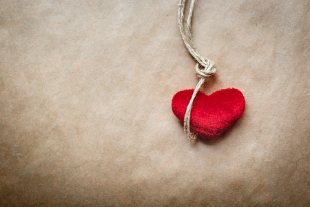plush: concept hangman knot with plush red heart on paper background Stock Photo