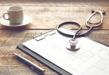 lugar de trabajo médico con un estetoscopio y taza de café en la mesa de madera