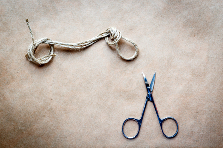 concept scissors cut the knot on rope on a background of paper Stock Photo