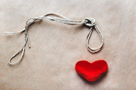 dangerous love: concept hangman knot with plush red heart on paper background Stock Photo