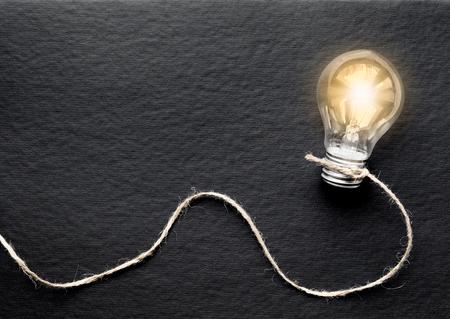 lit: concept of idea illustration lit lamp on black background close up