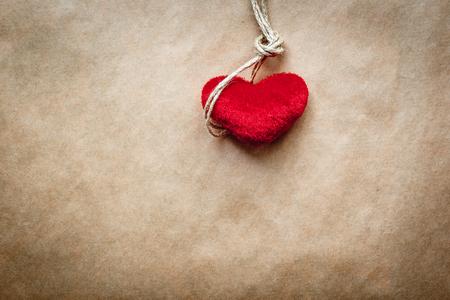 ahorcado: concepto del ahorcado nudo con el coraz�n rojo de peluche en el fondo de papel Foto de archivo