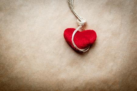 ahorcado: concepto del ahorcado nudo con el corazón rojo de peluche en el fondo de papel Foto de archivo