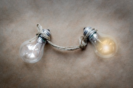 lit: concept of idea illustration lit lamp on paper background close up