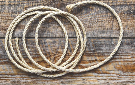 coiled rope: rope coiled on a wooden table close up