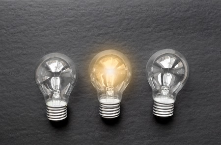 lit: three concept of idea illustration lit lamp on black background close up