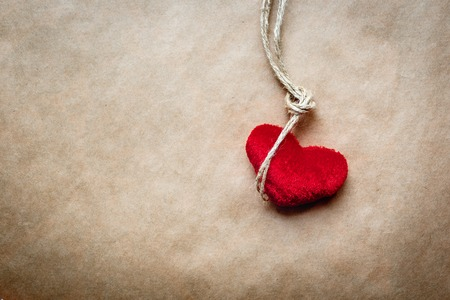 dangerous love: concept hangman knot with plush red heart  on kraft paper background