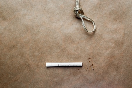 suffocation: concept hangmans knot on kraft paper background with cigarette close up Stock Photo