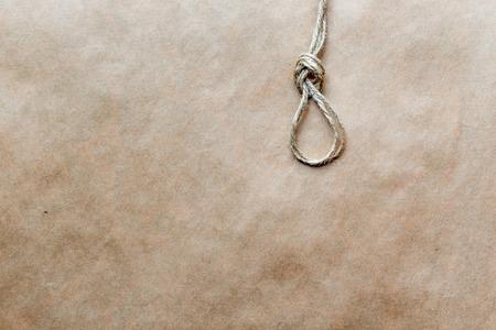 gibbet: concept hangmans knot on kraft paper backgroun close up soft light top view