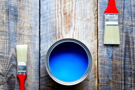 redecorating: painting at home with can of blue paint and two brush on wooden background top view Stock Photo