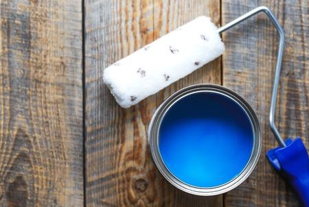 木製の背景平面図のペイント ローラーの青いペンキの缶で自宅塗装