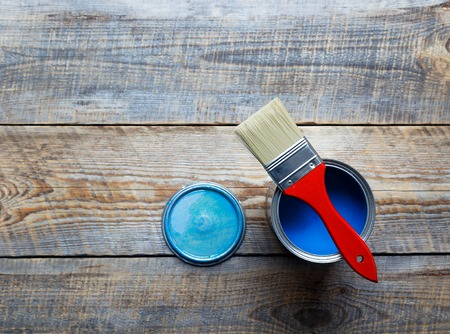 redecorating: painting  with open can of blue paint  and red brush on wooden background top view Stock Photo