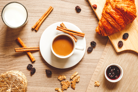 home life: breakfast at home on wooden table with cup of milk coffee, croissants, macaron top view Stock Photo