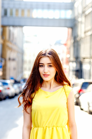 airfoil: young smiling girl on city streets in summer in yellow dress