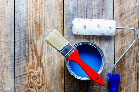 red paint roller: preparation for painting with can of blue paint and red brush with paint roller top view
